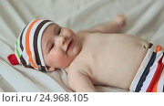 Купить «Funny four month old baby lying on his back and smiling. Dressed baby in striped shorts and cap», видеоролик № 24968105, снято 20 января 2017 г. (c) Mikhail Davidovich / Фотобанк Лори