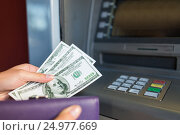 Купить «close up of hand withdrawing money at atm machine», фото № 24977669, снято 8 сентября 2016 г. (c) Syda Productions / Фотобанк Лори