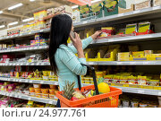 Купить «woman with food basket and smartphone at store», фото № 24977761, снято 2 ноября 2016 г. (c) Syda Productions / Фотобанк Лори
