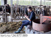 Купить «young man with tablet pc and cows on dairy farm», фото № 24977989, снято 12 августа 2016 г. (c) Syda Productions / Фотобанк Лори