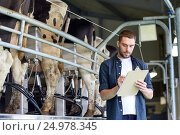 Купить «man with clipboard and milking cows on dairy farm», фото № 24978345, снято 12 августа 2016 г. (c) Syda Productions / Фотобанк Лори