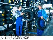 Купить «Mechanics working with new tires», фото № 24983629, снято 26 сентября 2018 г. (c) Яков Филимонов / Фотобанк Лори