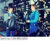 Купить «Mechanics working with new tires», фото № 24983653, снято 26 сентября 2018 г. (c) Яков Филимонов / Фотобанк Лори
