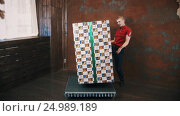 Illusionist in red shirt in studio use telekinesis make big present box levitate. Стоковое видео, видеограф Александр Багно / Фотобанк Лори