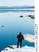 Рыбак средних лет на берегу озера зимой стоит и ждет поклевки, фото № 24989277, снято 29 декабря 2011 г. (c) Эдуард Паравян / Фотобанк Лори