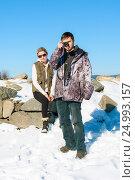 Серьезный фотографирующий юноша и женщина, сидящая на камнях, смотрят в кадр, фото № 24993157, снято 2 января 2012 г. (c) Эдуард Паравян / Фотобанк Лори