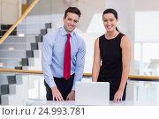 Купить «Business executives standing at desk with laptop», фото № 24993781, снято 3 ноября 2016 г. (c) Wavebreak Media / Фотобанк Лори