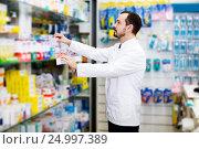 Купить «Male pharmacist searching for reliable drug», фото № 24997389, снято 14 декабря 2016 г. (c) Яков Филимонов / Фотобанк Лори
