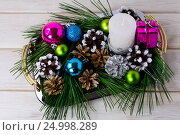 Купить «Christmas multicolored ornaments and candle centerpiece», фото № 24998289, снято 22 октября 2016 г. (c) TasiPas / Фотобанк Лори