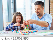 Купить «Beautiful little girl with her father playing with colored set for creativity», фото № 25002893, снято 8 января 2017 г. (c) Andrejs Pidjass / Фотобанк Лори