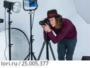 Купить «Photographer clicking a picture using digital camera», фото № 25005377, снято 1 сентября 2016 г. (c) Wavebreak Media / Фотобанк Лори