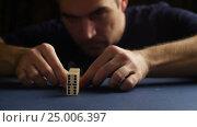Купить «Man set up the domino with hand. Domino effect», видеоролик № 25006397, снято 30 января 2017 г. (c) Сергей Кальсин / Фотобанк Лори