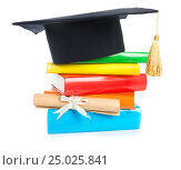 Купить «A mortarboard and graduation scroll, tied with red ribbon, on a stack of books», фото № 25025841, снято 27 марта 2015 г. (c) Валерия Потапова / Фотобанк Лори