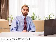 Businessman sitting at a desk looking to laptop. Стоковое фото, фотограф VictorStudio / Фотобанк Лори