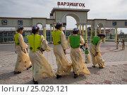 Купить «Девушки в национальных костюмах проходят мимо входа на стадион в городе Худжанд в Республике Таджикистан», фото № 25029121, снято 21 марта 2015 г. (c) Николай Винокуров / Фотобанк Лори
