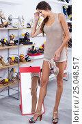 Купить «girl customer trying on chosen shoes in footwear department», фото № 25048517, снято 13 декабря 2017 г. (c) Яков Филимонов / Фотобанк Лори