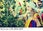 Купить «Young woman buying Xmas tree at festive fair», фото № 25055397, снято 27 января 2020 г. (c) Яков Филимонов / Фотобанк Лори