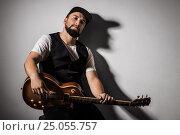 Купить «Handsome bearded musician playing guitar over gray background», фото № 25055757, снято 17 ноября 2016 г. (c) Marina Goncharova / Фотобанк Лори