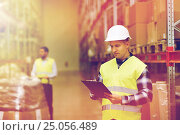 Купить «man with clipboard in safety vest at warehouse», фото № 25056489, снято 9 декабря 2015 г. (c) Syda Productions / Фотобанк Лори