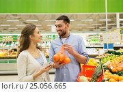 Купить «happy couple buying oranges at grocery store», фото № 25056665, снято 21 октября 2016 г. (c) Syda Productions / Фотобанк Лори