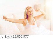young woman stretching in bed after waking up, фото № 25056977, снято 25 февраля 2016 г. (c) Syda Productions / Фотобанк Лори