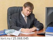 Купить «Мужчина в офисе пишет,   рядом налоговый кодекс и конверт с деньгами», фото № 25068045, снято 5 февраля 2017 г. (c) Гетманец Инна / Фотобанк Лори