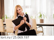 Attractive businesswoman with clipboard sitting in the office. Стоковое фото, фотограф VictorStudio / Фотобанк Лори