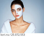 Купить «Gorgeous woman with cosmetic mask on her face. Photo of attractive brunette girl wearing white bathrobe. Wellness and Spa concept», фото № 25072553, снято 7 сентября 2016 г. (c) Роман Егошин / Фотобанк Лори