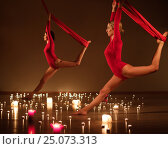 Купить «Two young girls in red performing aerial yoga in relaxing candle lights», фото № 25073313, снято 22 января 2017 г. (c) Andrejs Pidjass / Фотобанк Лори