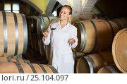 Купить «Woman checking ageing process of wine», фото № 25104097, снято 21 сентября 2016 г. (c) Яков Филимонов / Фотобанк Лори