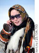 Купить «Carolina Serotetto, Nenet teenager wearing sunglasses and  traditional winter coat of reindeer fur holding smartphone. Yar-Sale district, Yamal, Northwest Siberia, Russia. April 2016.», фото № 25134793, снято 9 июля 2020 г. (c) Nature Picture Library / Фотобанк Лори