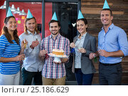 Купить «Portrait of businesspeople celebrating their colleagues birthday», фото № 25186629, снято 16 октября 2016 г. (c) Wavebreak Media / Фотобанк Лори