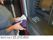 Купить «close up of hand withdrawing money at atm machine», фото № 25210853, снято 8 сентября 2016 г. (c) Syda Productions / Фотобанк Лори