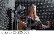 Купить «Girl with guitar in recording studio», видеоролик № 25225505, снято 23 октября 2018 г. (c) Raev Denis / Фотобанк Лори