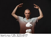Telekinesis - man making stones levitating. Стоковое фото, фотограф Гурьянов Андрей / Фотобанк Лори
