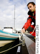 Купить «Man untying rib from marina pontoon, December 2008. Cowes, Isle of Wight. Model Released.», фото № 25402289, снято 24 апреля 2018 г. (c) Nature Picture Library / Фотобанк Лори
