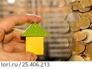Купить «Деревянный дом в руке на фоне денег и строительства», фото № 25406213, снято 12 февраля 2017 г. (c) Сергеев Валерий / Фотобанк Лори