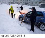 Люди откапывают машины из сугробов после снегопада (2017 год). Редакционное фото, фотограф Вячеслав Палес / Фотобанк Лори