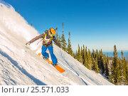 Купить «Freeride snowboarder slides down a steep slope at dawn», фото № 25571033, снято 9 декабря 2016 г. (c) Zakirov Aleksey / Фотобанк Лори