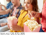 close up of happy friends eating popcorn at home. Стоковое фото, фотограф Syda Productions / Фотобанк Лори