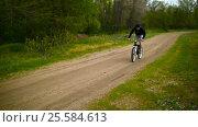 Купить «Cyclist Rides On A Bike On The Pathway», видеоролик № 25584613, снято 23 мая 2016 г. (c) Станислав Панкратов / Фотобанк Лори