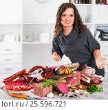 Купить «Woman costs near table on which sausages and smoked meat», фото № 25596721, снято 17 августа 2018 г. (c) Яков Филимонов / Фотобанк Лори