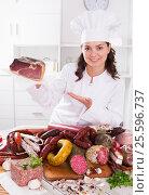 Купить «Girl shows sausages and smoked products», фото № 25596737, снято 17 августа 2018 г. (c) Яков Филимонов / Фотобанк Лори