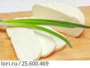 Cheese and green onion pens on wooden cutting board. Healthy valuable food. Стоковое фото, фотограф Евгений Пидеркин / Фотобанк Лори
