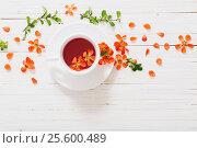 Купить «Red tea with flowers on white wooden background», фото № 25600489, снято 13 мая 2016 г. (c) Майя Крученкова / Фотобанк Лори