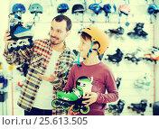 Купить «Young man and son boasting roller-skates», фото № 25613505, снято 21 декабря 2016 г. (c) Яков Филимонов / Фотобанк Лори