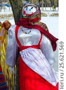 Масленичная кукла в цветастом платке и сарафане возле дерева и деревенского забора с кувшином. Стоковое фото, фотограф Ольга Коцюба / Фотобанк Лори