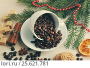 Coffee beans poured into a mug at the Christmas backdrop from sugar, tree branches, cinnamon. Стоковое фото, фотограф Денис Иванов / Фотобанк Лори