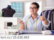 Купить «Young man tailor working on new clothing», фото № 25630493, снято 2 ноября 2016 г. (c) Elnur / Фотобанк Лори
