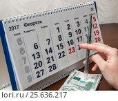 Купить «Шариковая ручка в руке и деньги на фоне календаря», эксклюзивное фото № 25636217, снято 6 февраля 2017 г. (c) Игорь Низов / Фотобанк Лори